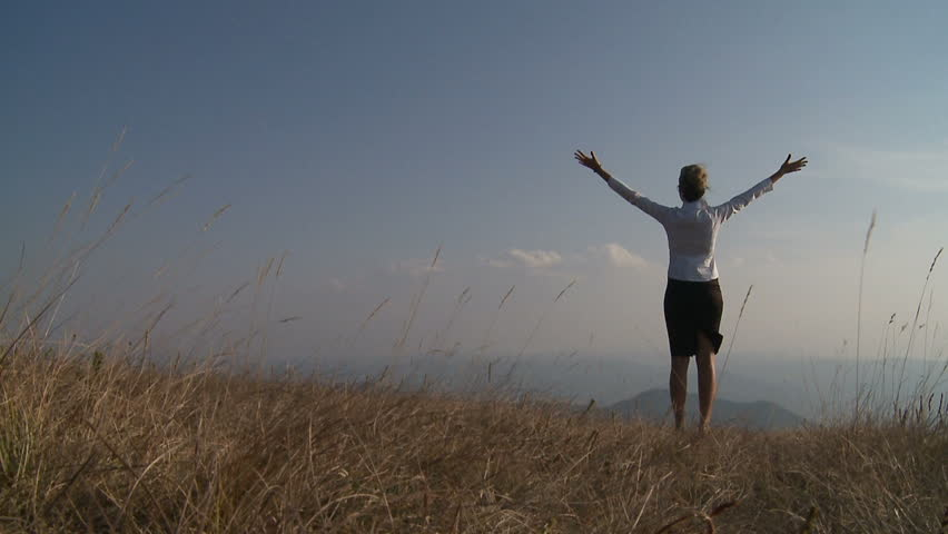 Business woman standing on cliff's edge and looking to a sky with raised hands. - HD stock footage clip