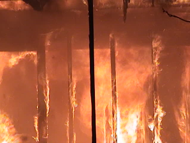 Flames engulfing the inside of a structure.