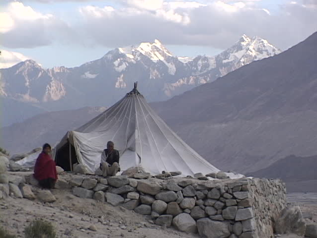 TIBET - CIRCA 2010: An unidentified man and woman sit outside their tent in the Himalayas circa 2010 in Tibet. - SD stock video clip