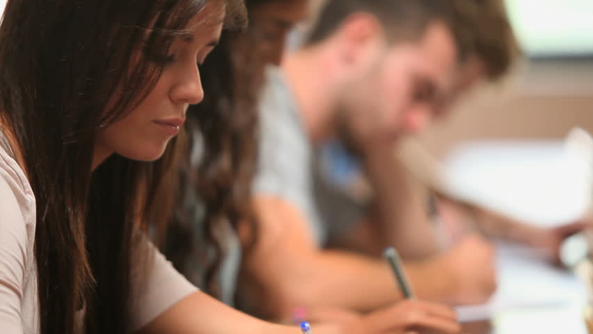 Close up of students writing in an amphitheater