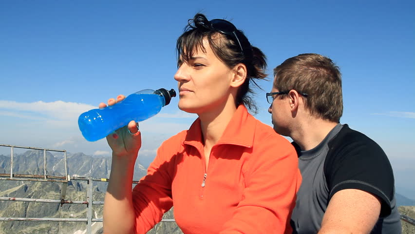 Female hiker drinking isotonic drink in the mountains, camera stabilizer shot - HD stock footage clip