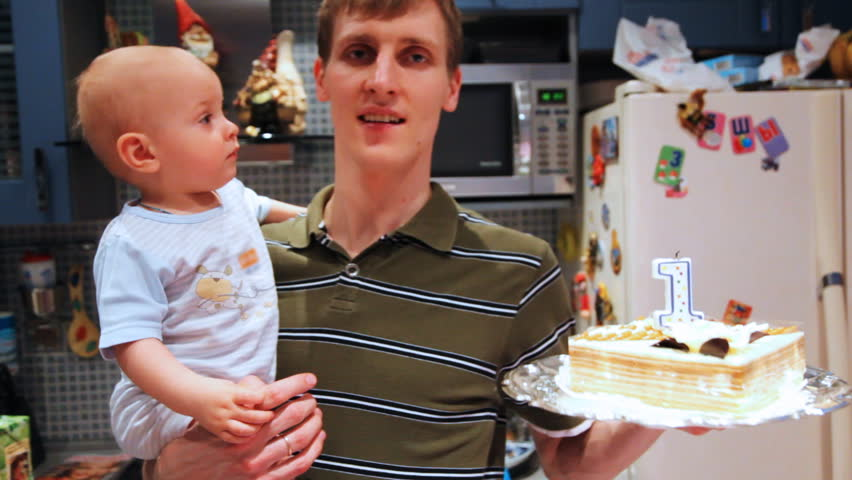 little baby in fathers hands try catch birthday cake on one year old - HD stock video clip