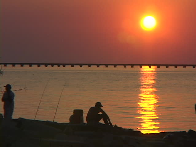 A fisherman catches a fish along the Gulf Coast. - SD stock footage clip