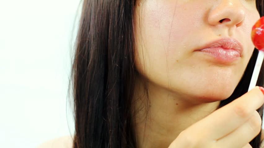 Woman licking sweet sugar candy closeup.