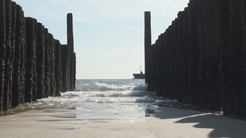 Sea breaker at the beach along the Dutch coach in the province of Zeeland with the waves rolling in - HD stock video clip