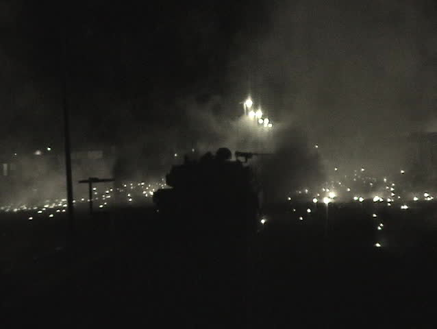 Abrams tanks fire into an Iraqi village.