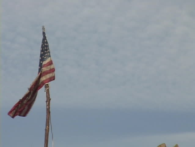 Zoom out from a flag planted in a pile of rubble left from Hurricane Katrina.