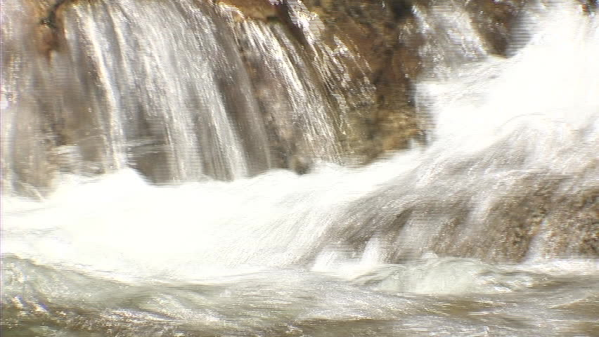 POV shot of a man's feet relaxing beside a small waterfall. - SD stock footage clip