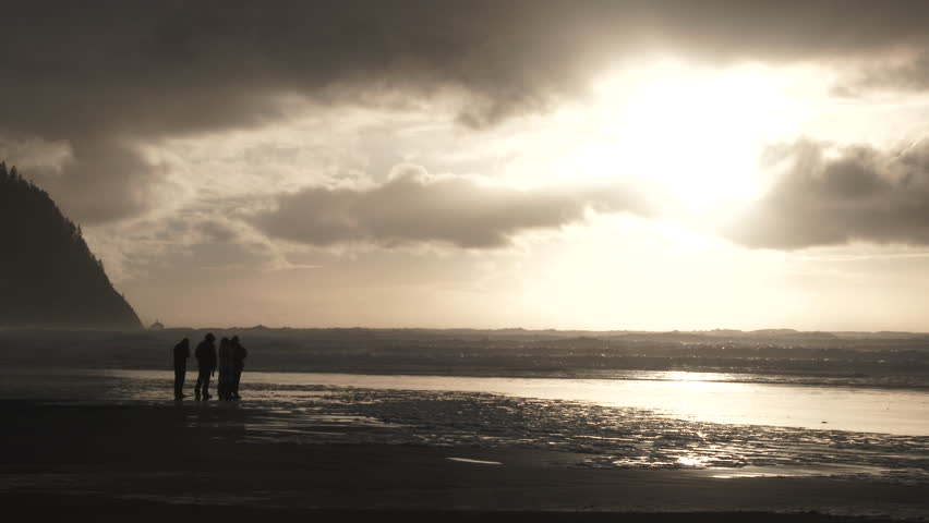 Group of unrecognizable people watch as the sun goes down over the Pacific Ocean from the Oregon Coast.