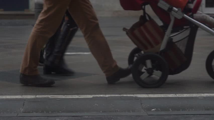 Slow motion video of unrecognizable people with baby carriage walking in the street. Autumn and winter shoes view
