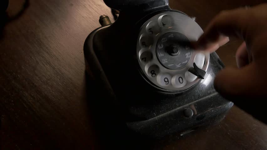 Someone is dialing the number on black dial telephone covered by dust and handset lying on an old brown wooden table / closeup / camera moving right - 4K stock video clip