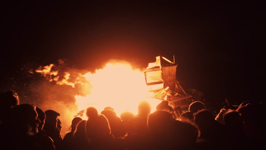 People watch big huge fire from wooden furniture and pallets in night. Unrecognizable, sparkles around