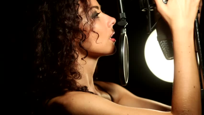 Beautiful young girl in profile sexy singing near the microphone recording studio | Shutterstock HD Video #14341096