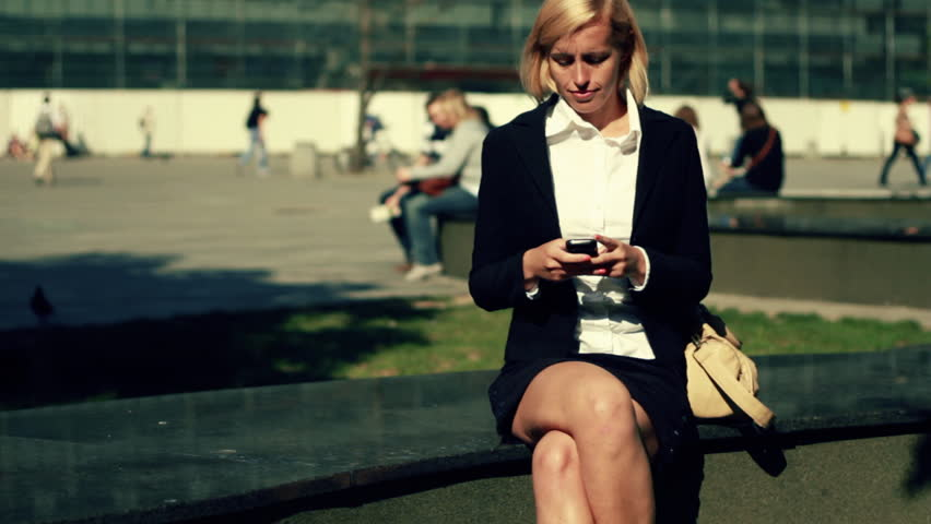 Businesswoman sending sms in the city and smiling, camera stabilizer shot - HD stock footage clip