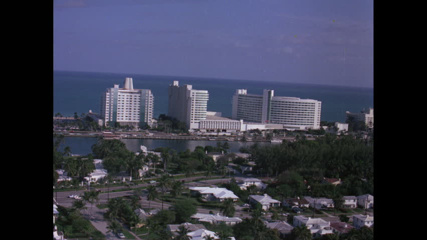 Aerial shot of Miami Beach, ocean, palm trees, and luxurious Hotel Fontainebleau, on a beautiful sunny day. Florida, 1964