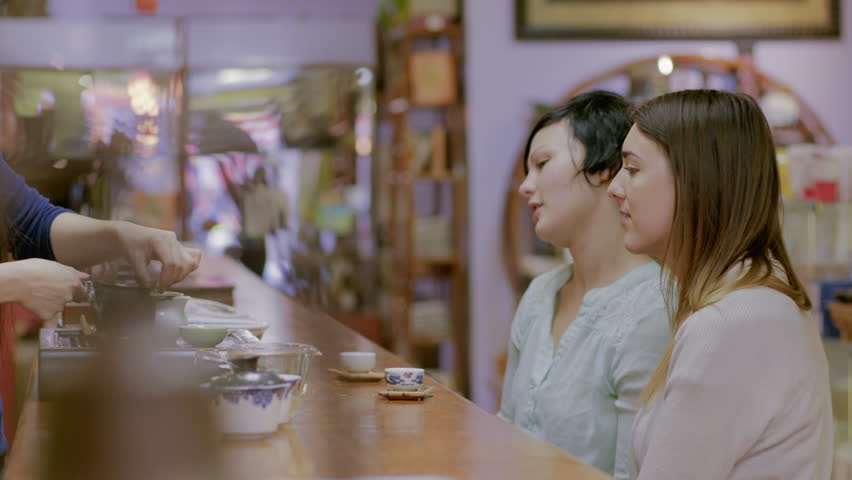 Two young caucasian girls being served tea by an Asian woman at a tea shop - HD stock video clip
