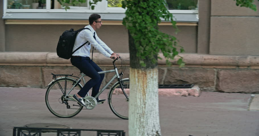 Mid adult office worker with backpack riding his bike to work, tracking shot