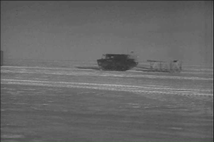 CIRCA 1950s - Vehicles transport an army group on a frozen snow road to Greenland in the 1950s. - SD stock video clip