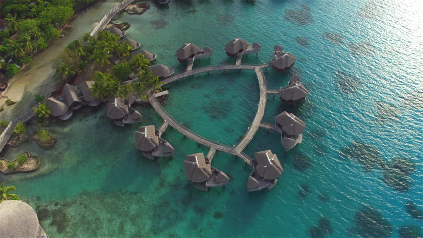 AERIAL: Flying above big luxury waterfront hotel on beautiful white sandy beach with deluxe overwater bungalows, restaurants and outdoors swimming pool overlooking the perfect turquoise blue lagoon - 4K stock footage clip