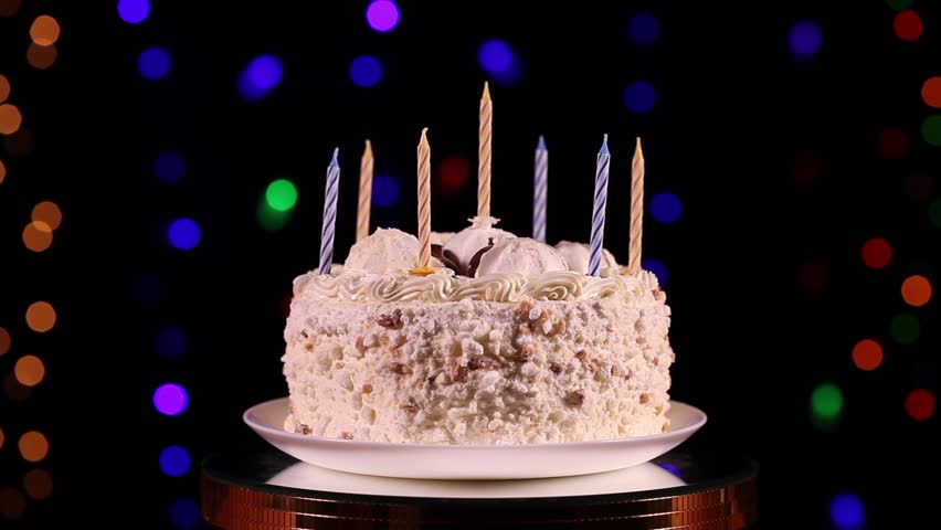 One's hand lit a candles of the birthday cake in front of black background