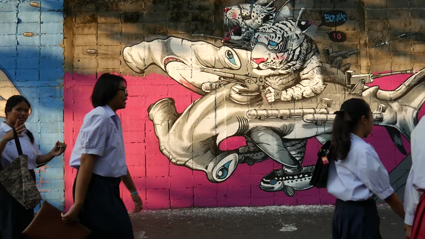 Bangkok, Thailand-February 5, 2016: View of street art on the wall in a Soi (lane) of Bangruk area of Bangkok. People walk past the art. Some come to take photos with the art.   - 4K stock footage clip