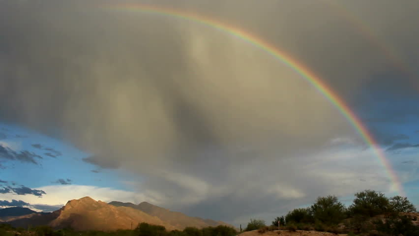 Fantastic double rainbow forms as rain shafts sweep over mountains with beautiful, blue sky and white puffy clouds beneath it. 1080p