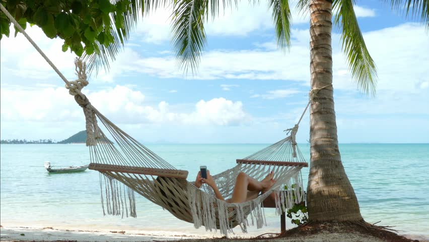 Woman using mobile phone in a hammock on the beach | Shutterstock HD Video #14566690