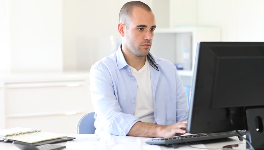 Portrait Of Office Worker Man Sitting At Office Desk Using Laptop ...