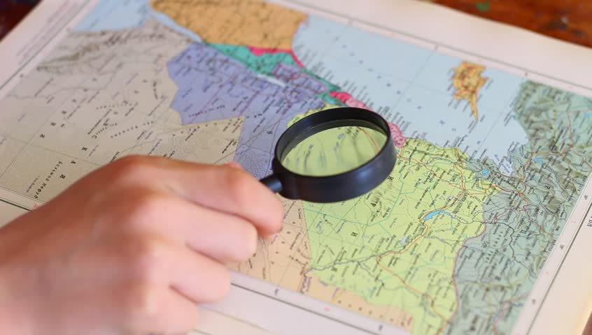A person is studying map of Syria with a magnifying glass