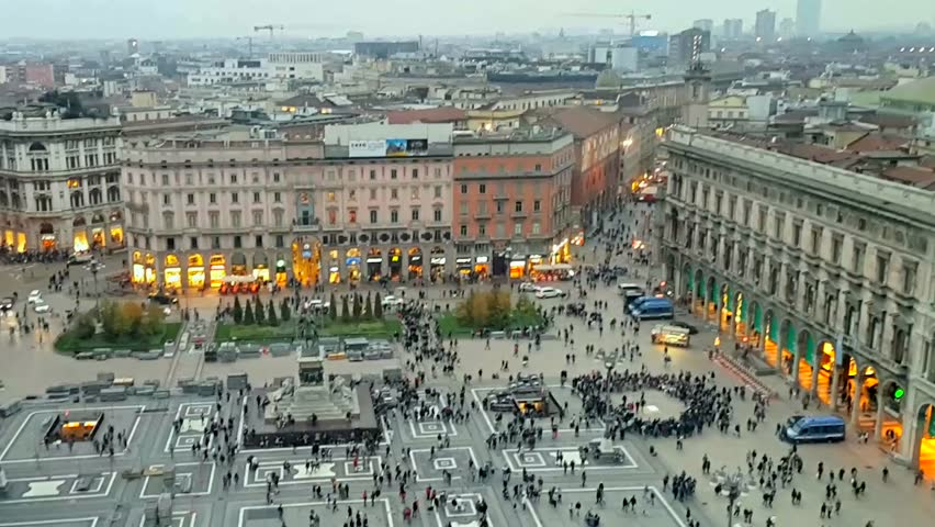 Italy. Autumn evening in Milan. Lots of people walking in front of the Duomo Cathedral. Illuminated shop windows around the perimeter. In the center - a monument to Victor Emmanuel II.  - HD stock video clip