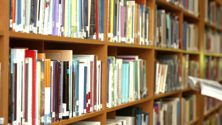 Student reading a library book by the book shelf | Shutterstock HD Video #14690593