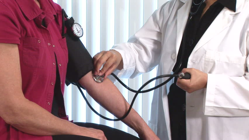 young doctor giving a blood pressure exam to a patient - HD stock video clip