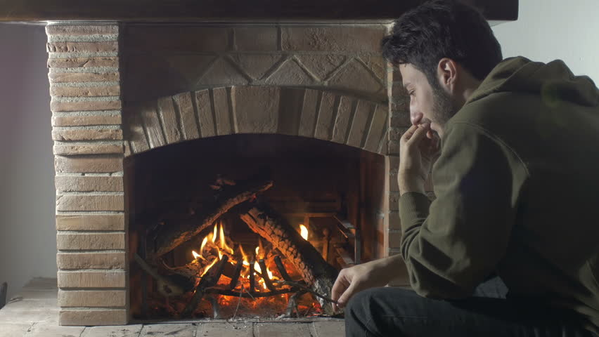 sad and mounrful guy sat in front of a fireplace - 4K stock footage clip