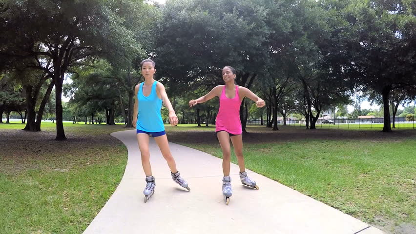 Young active multi ethnic American girls rollerblading outdoor - HD stock video clip