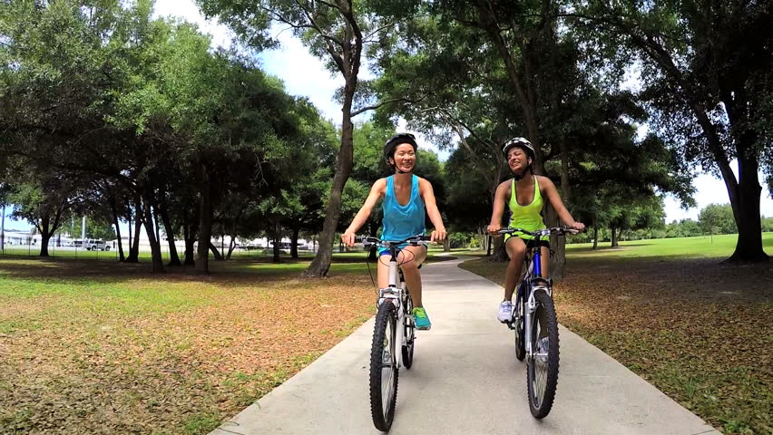 Young slim multi ethnic females riding bicycles in park - HD stock footage clip
