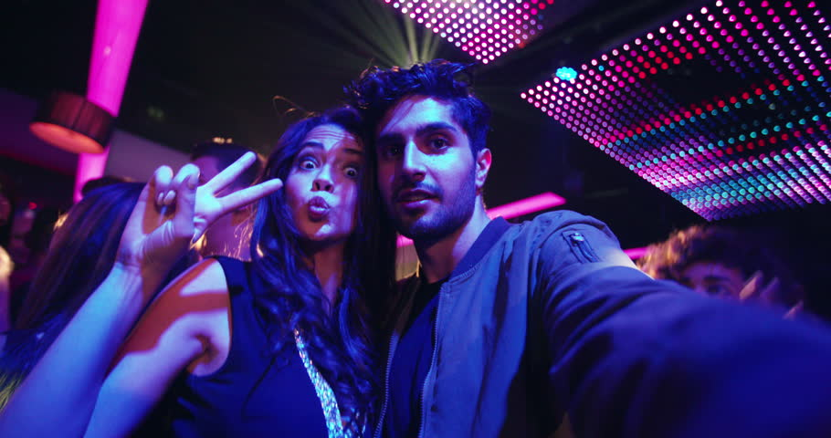 Fashionable friends at nightclub taking selfies and pulling faces for the photo with people, music and disco lights in the background of the party in the night club