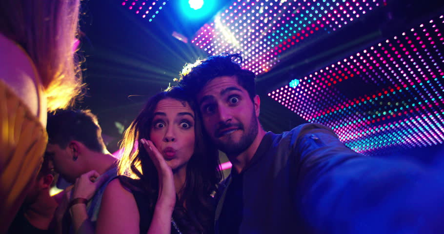 Fashionable friends at nightclub party taking selfies and pulling faces for the photo with people, music and disco lights in the background | Shutterstock HD Video #14730877