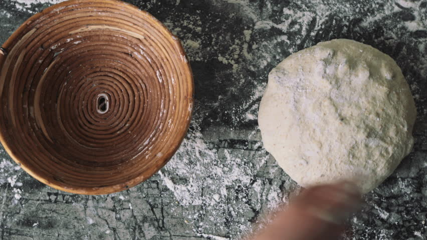 Female working with the dough. Putting the sourdough into the wooden rise basket