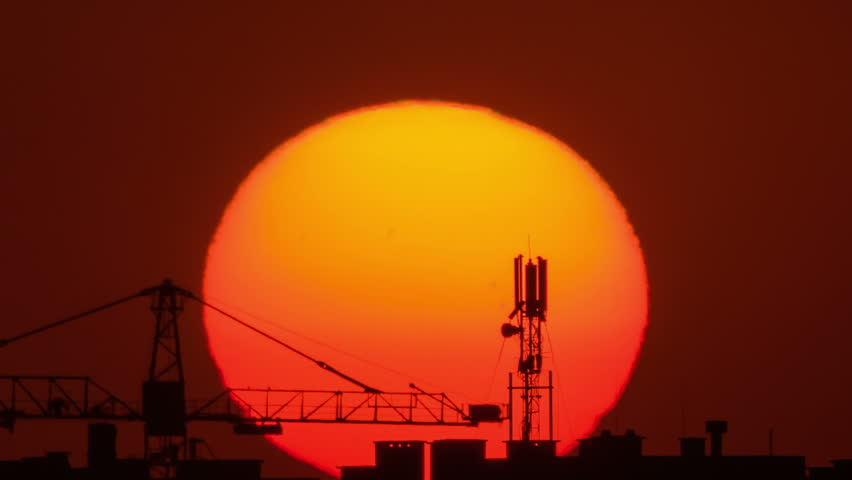 Time-lapse of solar disk moving behind tower crane and cell tower on building silhouettes  - HD stock video clip