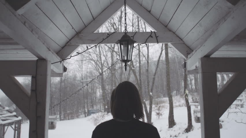 Handsome young man in black sweater standing back near the old wooden house. Winter scene of long-haired man standing on the porch of an old wooden house. Snowy background. Rear view, slow motion. | Shutterstock HD Video #14841154