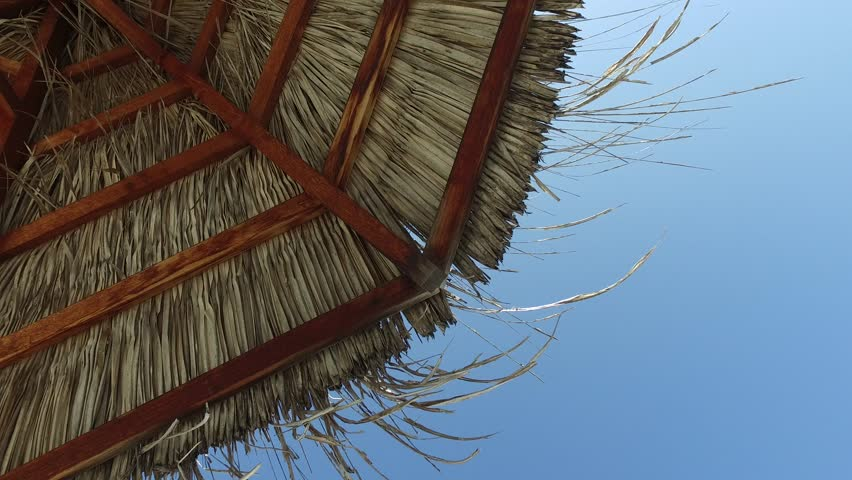 travel, tourism, vacation, beach and summer holidays concept - palapa or bungalow straw shed over blue sky - 4K stock footage clip