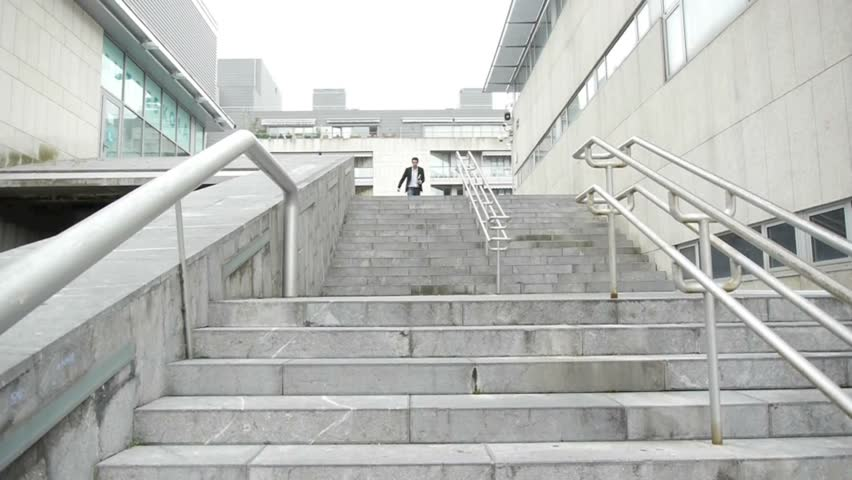 Man running down stairs in town - HD stock video clip