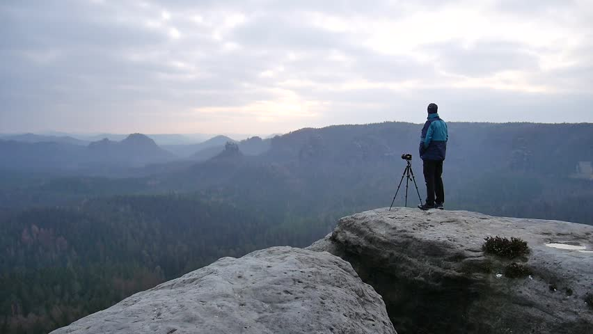 Photographer in blue jacket at tripod  on rocky view point and taking photos of misty morning landscape. Hike in rocks. Melancholic autumn morning.  | Shutterstock HD Video #14871799
