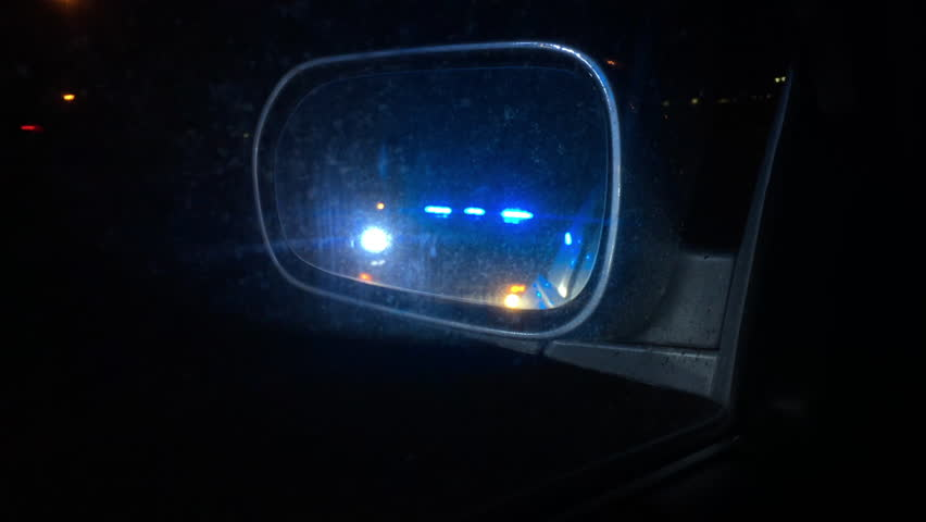 Police Lights Flashing In Side View Mirror Of Car Stock