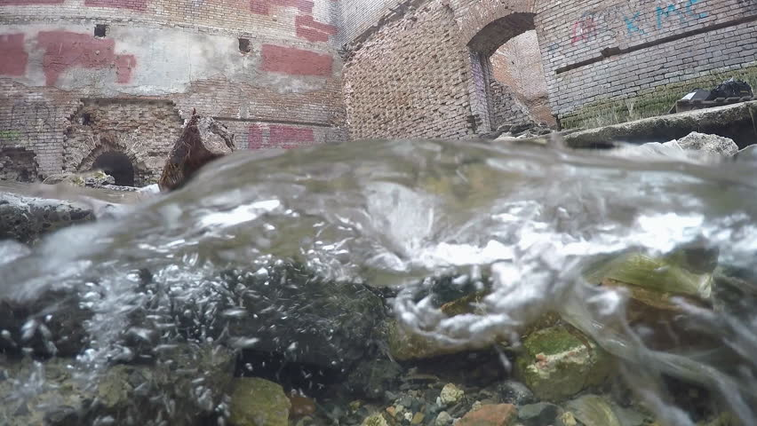Underwater split: beautiful pure fresh water waterfall flowing from old destroyed house. - HD stock footage clip
