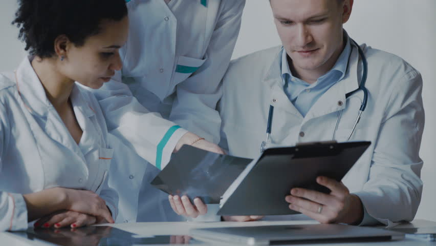 Healthcare, medical: Group of multi-ethnic doctors discussing and looking x-ray in a clinic or hospital. UHD 4K - 4K stock footage clip