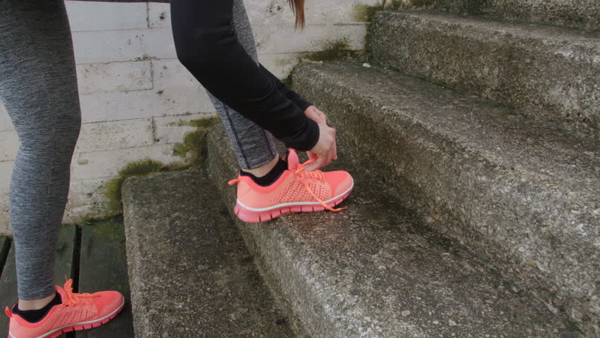 Female runner stop for lacing sport shoes and keep running upstairs. - 4K stock video clip
