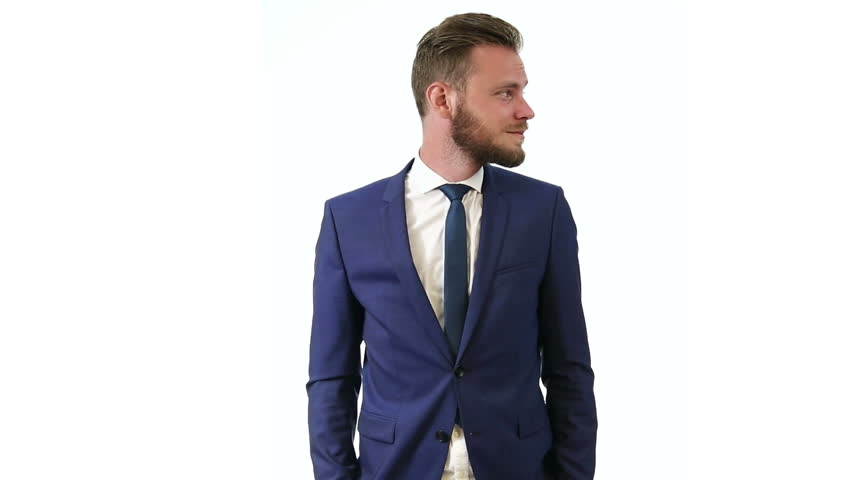 An attractive businessman in a blue suit, white shirt and blue tie, standing looking at camera with a white background. Focused and intense. - HD stock video clip