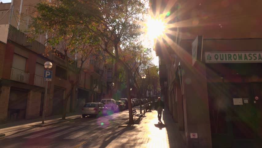 BARCELONA, SPAIN - FEBRUARY 25, 2016: Shaded and sunny street come upwards, truck shot along alley. Unidentified man walk down at sideway, smooth camera slide and cross driveway. Carrer Del Centre