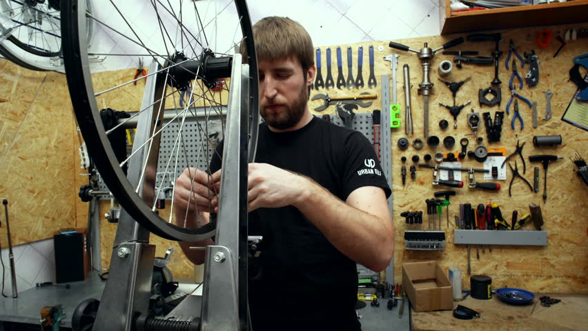 Mechanic repairing wheel in bicycle's workshop. Close up